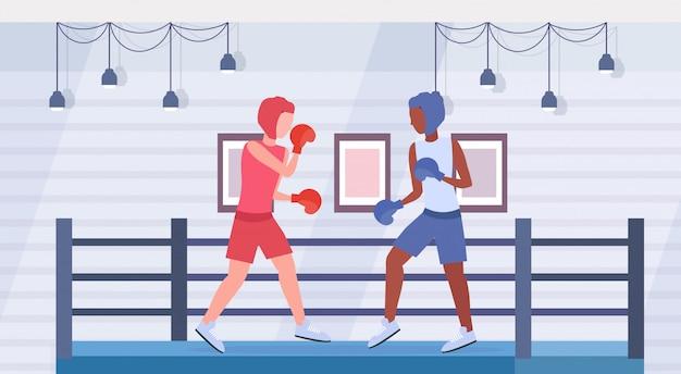 Boksers oefenen thai boksen paar mix race vechters in handschoenen en beschermende helmen oefenen samen vechten club ring arena interieur gezonde levensstijl concept plat