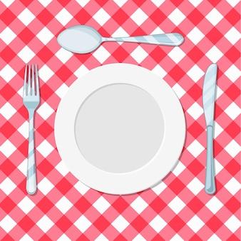 Bordmes, lepel en vork op een rood tafelkleed in een kooi