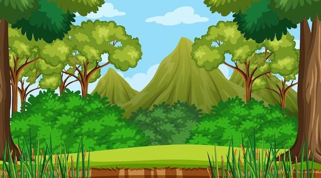 Bosscène met verschillende bosbomen en bergachtergrond