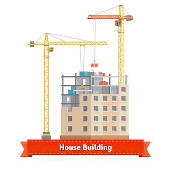 Bouw van een huis met torenkranen