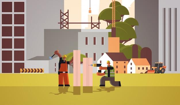Bouwers paar met behulp van boor en hummer mix race werklieden timmerlieden team boorgat hameren spijker in houten plank bouwconcept bouwplaats achtergrond volledige lengte horizontaal