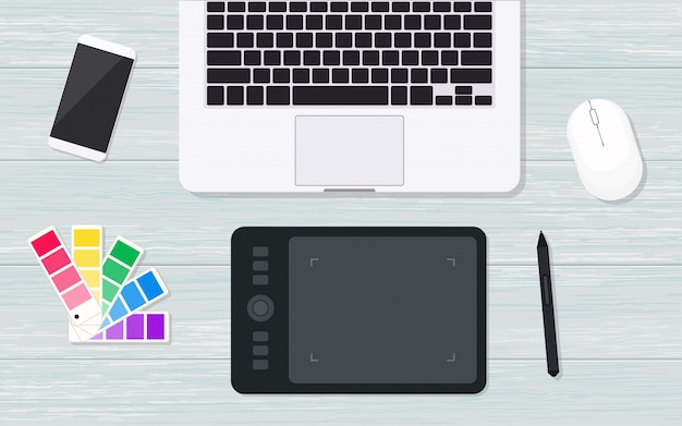 Bovenaanzicht designer werkplek met grafisch tablet. plat lag op houten achtergrond