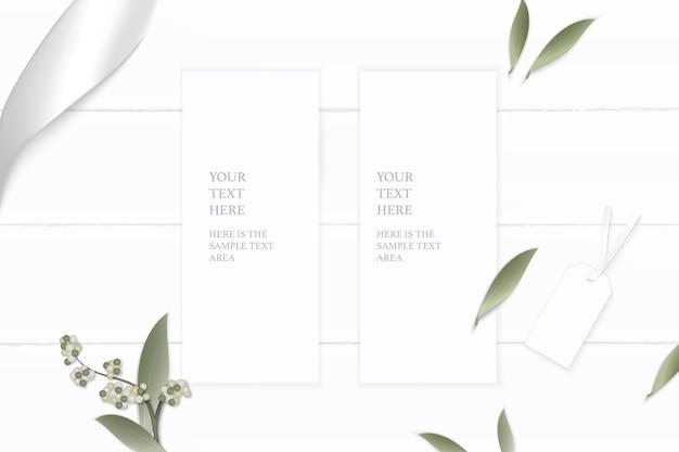 Bovenaanzicht elegante witte samenstelling papier bloem blad tag en zilveren lint op houten achtergrond.
