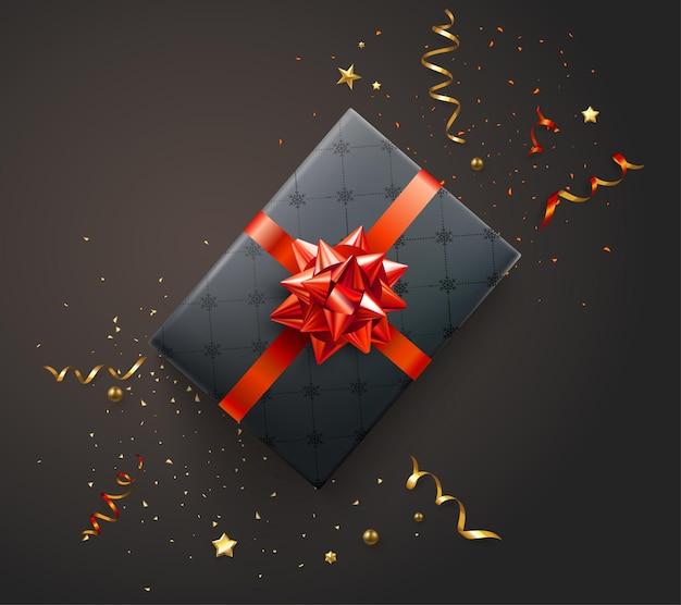 Bovenaanzicht geschenkdoos met rode strik en confetti