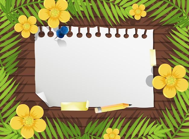 Bovenaanzicht van blanco papier op tafel met bladeren en gele bloem-elementen