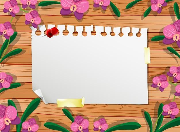 Bovenaanzicht van blanco papier op tafel met bladeren en roze orchideeën elementen