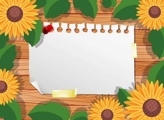 Bovenaanzicht van blanco papier op tafel met bladeren en zonnebloem elementen