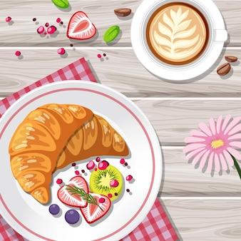 Bovenaanzicht van croissant met een koffiekopje op tafel