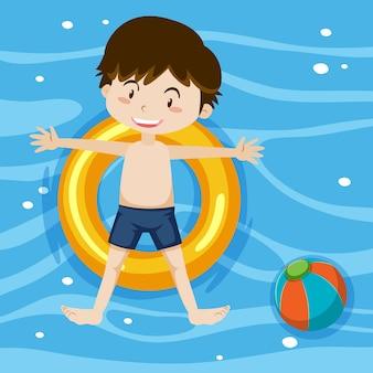 Bovenaanzicht van een jongen die op de zwemring op de achtergrond van het zwembad ligt