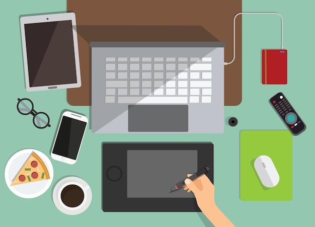 Bovenaanzicht van grafisch ontwerper werkplek op achtergrond. platte ontwerp van werkruimte met laptop, koffie, pizza