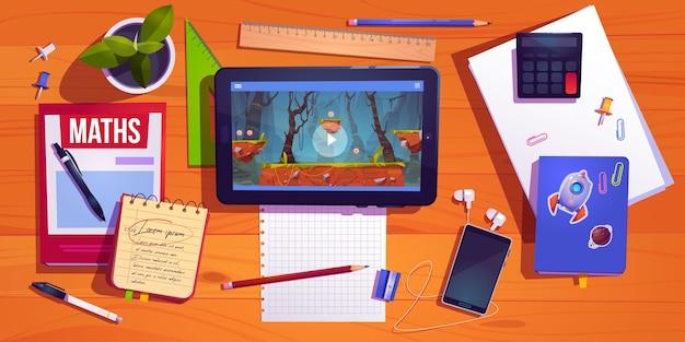 Bovenaanzicht van het studentenbureau, de tafel van de tiener thuiswerkplek met het bestuderen van briefpapiertablet met computerspel