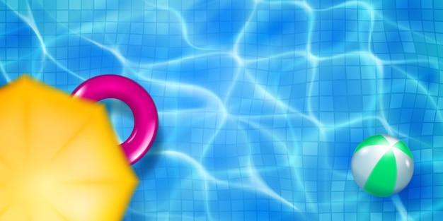 Bovenaanzicht van het zwembad met mozaïektegels, opblaasbare ring, bal en paraplubanner