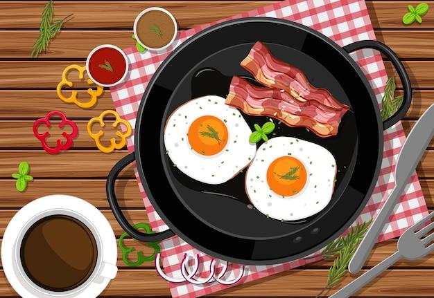 Bovenaanzicht van ontbijtmaaltijd met gebakken eieren en spek in een pan op de tafelachtergrond
