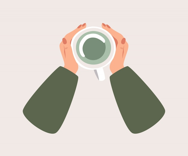 Bovenaanzicht verwarmt een kopje groene thee menselijke handen.
