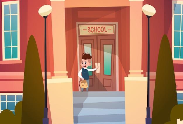 Boy opening school door pupil ga naar het klaslokaal