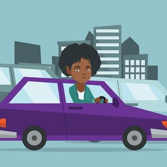 Boze afrikaanse vrouw in auto die in opstopping wordt geplakt.