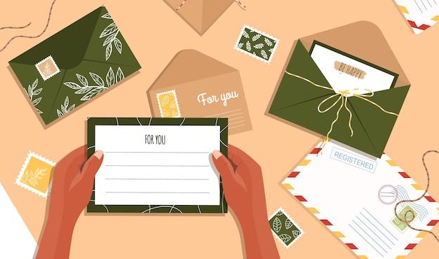Brief in de hand. enveloppen en ansichtkaarten op tafel. bovenaanzicht van de werkruimte.