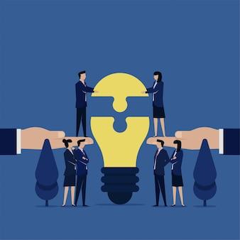 Business platte team zet laatste stukje idee lamp puzzel metafoor van het samenwerken.