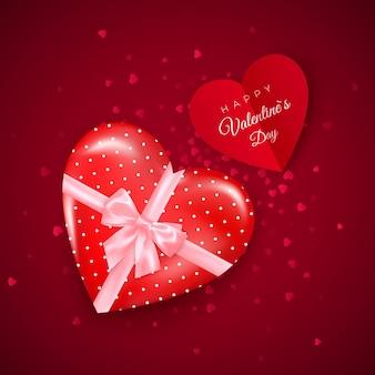 Cadeau in hartvormige doos met roze zijden strik en valentijnsdag wenskaart.