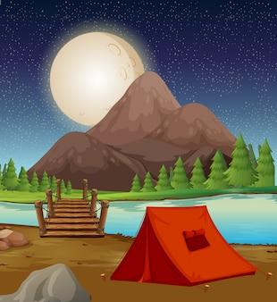 Camping met tent bij de rivier 's nachts