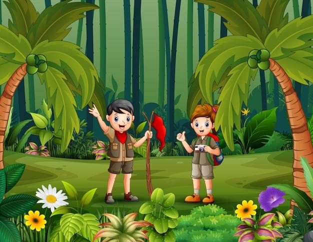 Cartoon de verkenner jongen en meisje wandelen in het bos