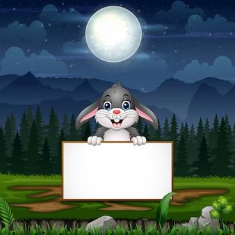 Cartoon een konijn met leeg teken onder de volle maan