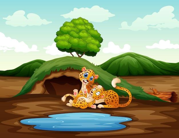 Cartoon een moeder cheetah met haar welp die in de natuur speelt