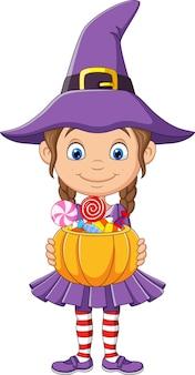 Cartoon heksenmeisje houdt een pompoenmand met snoepjes