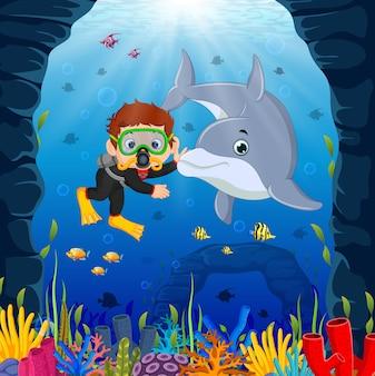 Cartoon jongen duiken in de zee met dolfijn