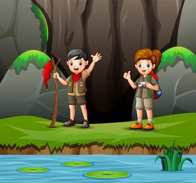 Cartoon jongen en meisje scout in de natuur