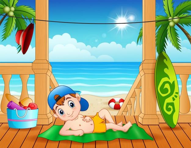 Cartoon jongen ligt op het houten terras