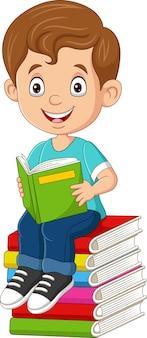 Cartoon kleine jongen die een boek leest op de stapel boeken