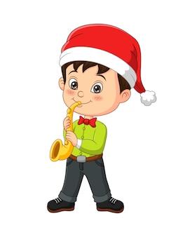 Cartoon kleine jongen in kerstkostuum die trompet speelt