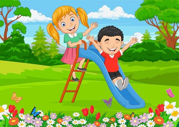 Cartoon kleine kinderen spelen glijdend in het park
