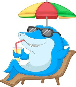 Cartoon schattige haai zit en houdt een drankje vast