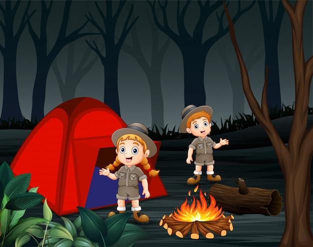 Cartoon van twee dierenverzorgers kamperen in een donker bos