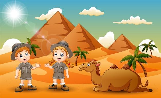 Cartoon van twee kinderen die een kameel in de woestijn hoeden
