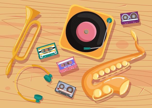 Cassettebandjes, vinylspeler en muziekinstrumenten op tafel.
