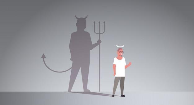 Casual man met nimbus kiezen tussen goede en kwade schaduw van de duivel