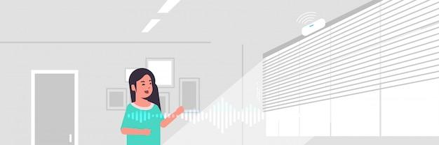 Casual vrouw met behulp van slimme luidspreker spraakherkenning geactiveerde digitale assistent