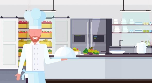 Chef-kok bedrijf overdekte schotel met schotel eten koken en culinaire concept moderne commerciële restaurant keuken interieur mannelijke cartoon karakter portret horizontale flat