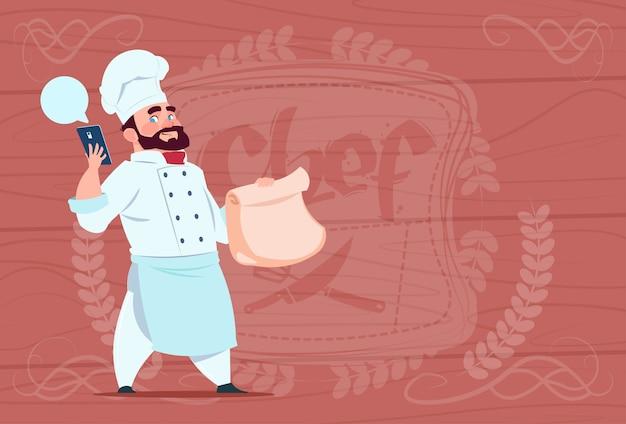 Chef-kok cook holding packet met voedsel en mobiele telefoon restaurant levering concept chief over houten gestructureerde achtergrond