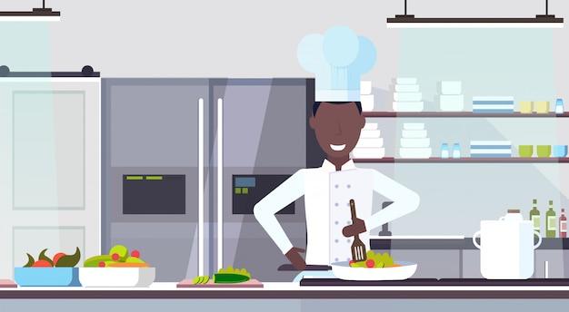 Chef-kok koken schotel mannelijke kok bereiden van voedsel culinaire concept moderne commerciële restaurant keuken interieur portret horizontale vlakte
