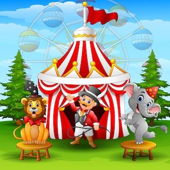 Circusolifant en tammer op de achtergrond van de circustent
