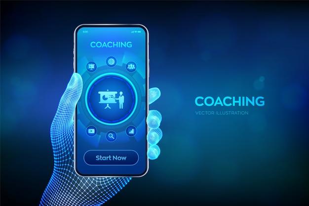 Coaching en mentoring concept op virtueel scherm. webinar, online trainingen. onderwijs en e-learning. close-upsmartphone in draadframe hand.