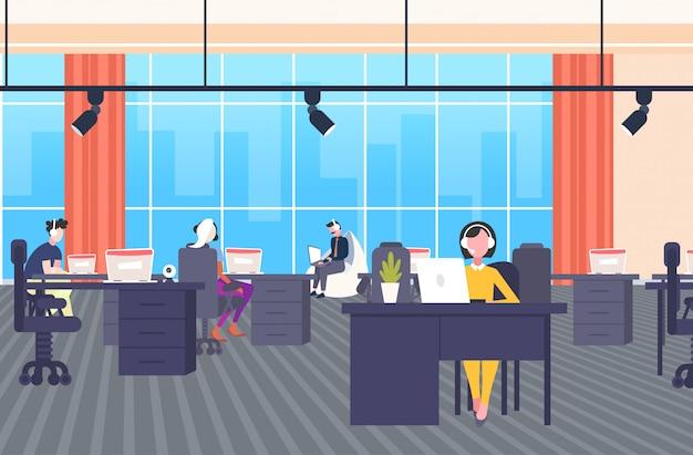 Collega's in hoofdtelefoon exploitanten zitten op bureaus werkplek callcenter concept co-werken open ruimte modern kantoor interieur horizontale banner volledige lengte