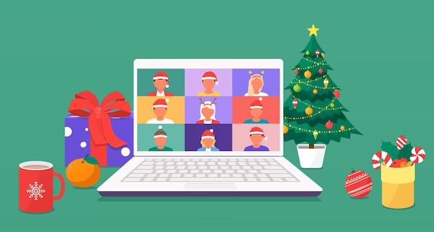 Collega's praten met elkaar op een laptopscherm via videogesprek. mannen en vrouwen met nieuwjaarsmutsen ontmoeten elkaar via videoconferentie en bespreken nieuwjaarsvakanties, kerstboomversieringen, geschenken.