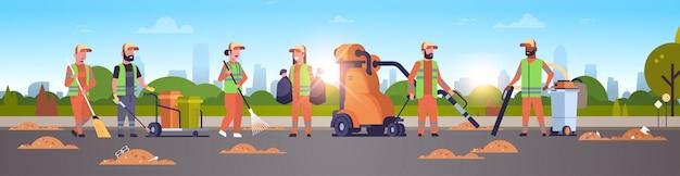 Conciërges team vuilnis reinigers verzamelen met behulp van stofzuiger