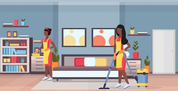 Conciërges vrouwen schoonmakers in uniform samen te werken afro-amerikaanse meisjes met behulp van stofzuiger en stofdoek schoonmaak service concept moderne slaapkamer interieur plat volledige lengte horizontaal