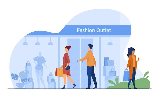 Consumenten lopen langs de straat in de buurt van kledingwinkel